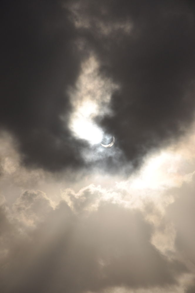 Solar Eclipse Seen Through Clouds Over Palm Cove, Australia