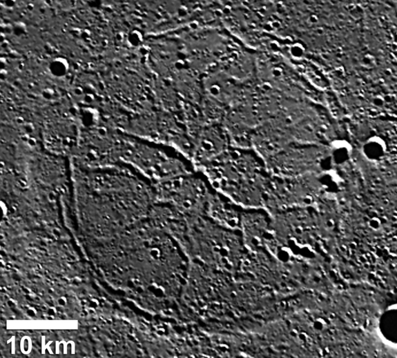 Wrinkle ridges and depressed troughs combine in this depressed crater in the Goethe basin on Mercury. The troughs, up to 2 kilometers wide, crosscut the outer ridge ring.