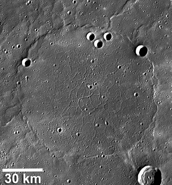 This Messenger photo of Mercury shows wrinkle ridges around a network of troughs that formed when the volcanic plains were stretched apart. The wrinkle-ridge ring, about 100 km in diameter, is formed over the rim of a so-called ghost crater.