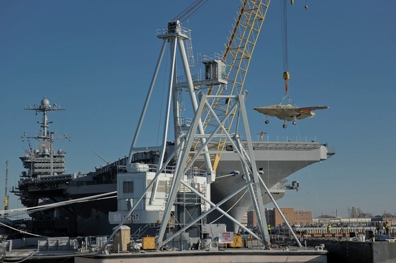 The U.S. Navy's X-47B drone is hoisted aboard the aircraft carrier USS Harry S. Truman in preparation for flight testing at sea.