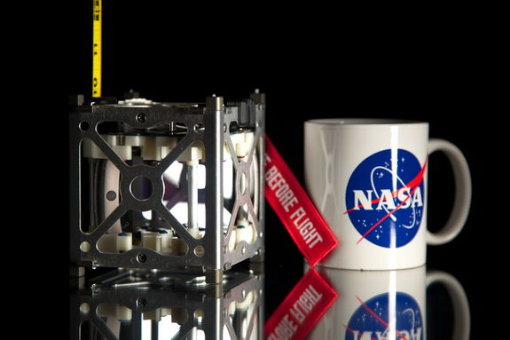 NASA's novel Phonesat 1.0 satellite is seen next to a coffee mug for size comparison. A trio of CubeSats makes up the innovative PhoneSat Project to be launched in 2013.