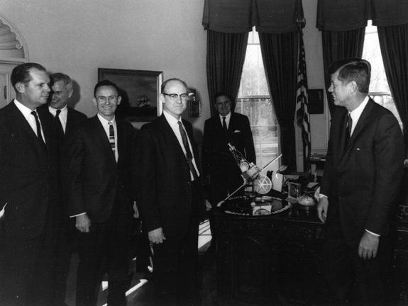 This 1961 photo shows Dr. William H. Pickering, (center) JPL director, presenting a Mariner spacecraft model to President John F. Kennedy, (right). NASA Administrator James Webb is standing directly behind the Mariner model.