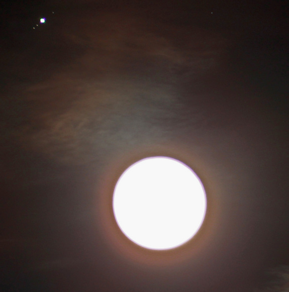 "Astrophotographer Victor Rogus intentionally over-exposed this image of the moon and Jupiter in conjunction to capture three of Jupiter's Galilean Moons.  He zoomed in using a Baader Planetarium Vario-finder (61mm x 250mm) as a lens at f4.1 exposure time, 0""4 of a second and ISO at 200."