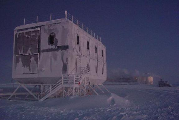 An elevated dorm at NSF's Amundsen-Scott South Pole Station is shown with a new elevated station in the background. The photo was taken on Sept. 9, 2005. The Pole is currently experiencing a period known as civil twilight; the sun will not rise above the horizon until late September.