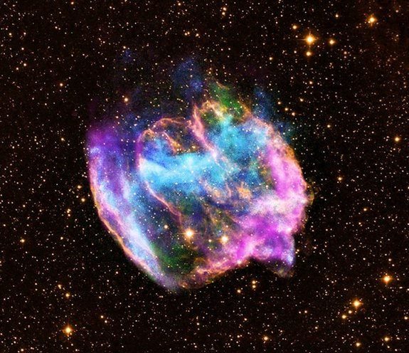 The highly distorted supernova remnant W49B in this image may contain the youngest black hole in the Milky Way galaxy. The image combines X-rays from NASA's Chandra X-ray Observatory in blue and green, radio data from the NSF's Very Large Array in pink, and infrared data from Caltech's Palomar Observatory in yellow. Image released Feb. 13, 2013.