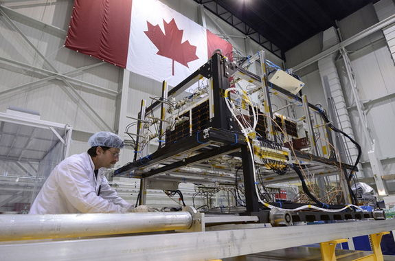 A technician removes the infrared test rig surrounding  the asteroid-hunting NEOSSat after the final thermal vacuum test at the David Florida Laboratory located in Ottawa, Ontario. NEOSSat is a dual-mission microsatellite designed to detect potentially hazardous Earth-orbit-crossing asteroids and track objects that reside in deep space. It is also the first implementation of Canada's generic multi-mission microsatellite bus. It will launch aboard an Indian Polar Satellite Launch Vehicle on Feb. 25, 2013.