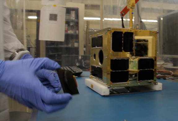 Cordell Grant putting the finishing touches to the first BRITE satellite at UTIAS-SFL. The tiny nanosatellite, designed to study the brightest stars in the night sky, is one of seven spacecraft launching on India's Polar Satellite Launch Vehicle C20 mission on Feb. 25, 2013.