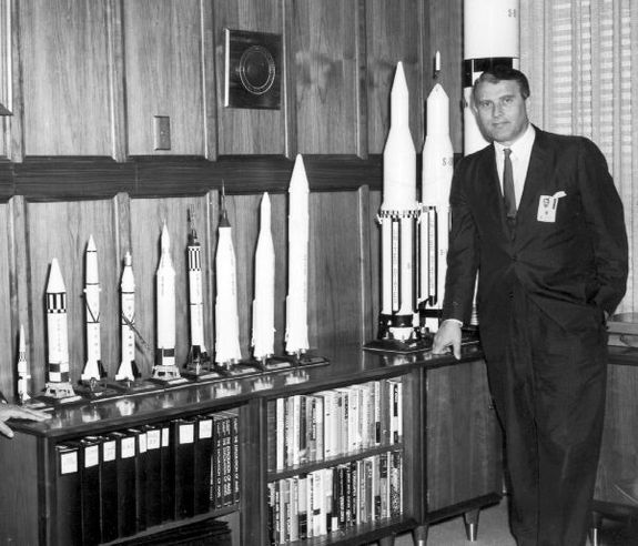 In this photo, probably taken in 1962, Dr. Von Braun is shown in his office at Marshall Space Flight Center with a display of rocket models.