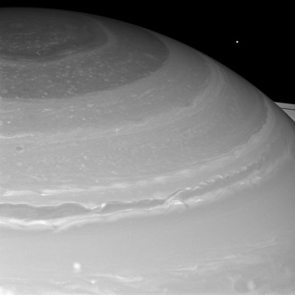 Saturn and its north polar hexagon dwarf Mimas as the moon peeks over the planet's limb. Saturn's A ring also makes an appearance on the far right. Image released March 18, 2013.