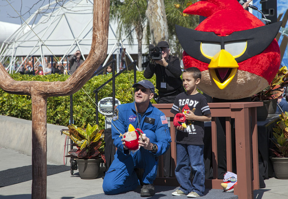 At NASA's Kennedy Space Center Visitor Complex in Florida, NASA astronaut Don Pettit uses a giant slingshot to launch a plush Angry Bird character during the grand opening of the new Angry Birds Space Encounter. Standing behind Pettit is Red Bird, one of the Angry Bird characters. Image was released March 22, 2013.