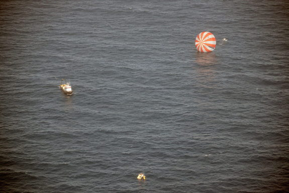 Recovery boats approach Dragon after splashdown into the Pacific Ocean on March 26, 2013. Dragon returned from the International Space Station.