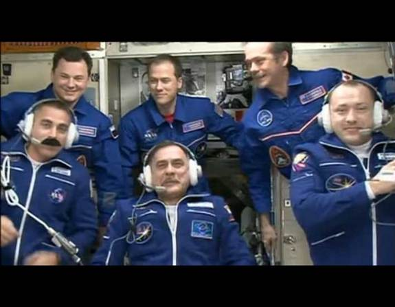 NASA astronaut Chris Cassidy (bottom left) wears a felt mustache to match the Canadian astronaut Chris Hadfield on board the International Space Station