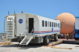 "NASA's space shuttle crew transport vehicle (CTV), a modified airport ""people mover,"" is loaded onto a barge at Kennedy Space Center for the Wings of Dreams Aviation Museum on April 24, 2013."