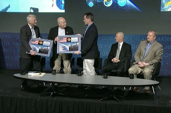International Space Station Expedition 34 commander Kevin Ford (right) presents Skylab astronauts Owen Garriott (left) and Gerald Carr with space-flown flags to mark the 40th anniversary of their missions on board America's first space station, May 13, 2013 at NASA Headquarters in Washington, D.C.