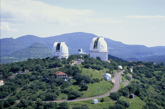 The two large domes in the foreground house the 2.1-meter (82-inch) Otto Struve Telescope (left) and the 2.7-meter (107-inch) Harlan J. Smith Telescope (right). Between these two, the Hobby-Eberly Telescope (HET) can be seen, atop neighboring Mt. Fowlkes