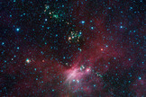 In this view showing a portion of sky near Canis Major, infrared data from NASA's Spitzer Space Telescope are green and blue, while longer-wavelength infrared light from NASA's Wide-field Infrared Survey Explorer (WISE) are red.