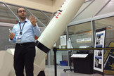 "An engineering model of the robotic Canadarm sits in the CSA's ""high bay"" of equipment behind Mario Ciaramicoli, the agency's operations manager."