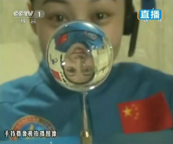 This screengrab from television taken on June 20, 2013 shows female astronaut Wang Yaping, one of the three crew members of Shenzhou-10 spacecraft, making a water ball in space during a lecture to students on Earth, aboard China's space module Tiangong-1.