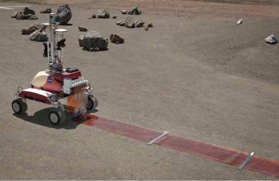 NASA's K10 rover at the Ames Research Center in Moffett Field,Calif., performs  a surface survey with its cameras and laser system, and then deployed a simulated polymide antenna while being controlled by an astronaut in space during a June 2013 test.
