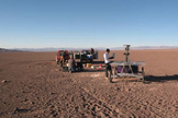 The Zoë rover being checked out at the start of its Atacama Desert traverse in June 2013. In the background are the two 4x4 trucks that were used to follow the robot. The engineers stay within communication range to monitor the robot but try to say out of view as much as possible.