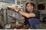 On board the International Space Station, Expedition Six flight engineer Donald Pettit uses a chemical/microbial analysis bag to collect water samples from the Potable Water Heater in Russia's Zvezda Service Module.