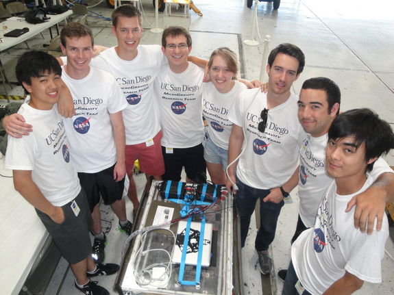 Engineering students with the UCSD Microgravity Team from the University of California, San Diego, stands near their biofuel experiment to test weightless flames ahead of a NASA Microgravity University flight at Ellington Field in Houston. The are: (clockwise from left): Joshua Siu, Sam Avery, Jack Goodwin, Andrew Beeler, Daneesha Kenyon, Joshua Sullivan, Nico Montoya, and Victor Hong. NASA mentor Christina Gallegos is not pictured. Image taken on July 18, 2013.