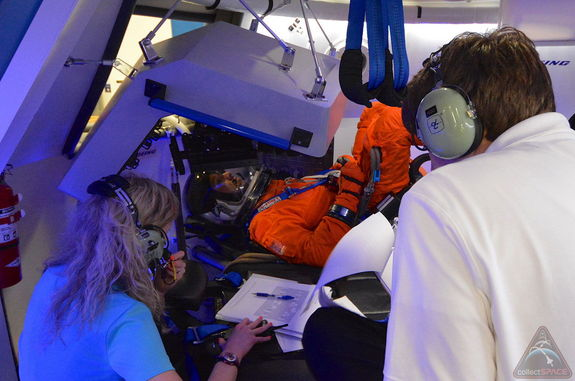 NASA astronaut Randy Bresnik, wearing a shuttle-era Advanced Crew Escape Suit (ACES) pressure suit, takes part in a fit check inside Boeing's CST-100 space capsule mockup, July 22, 2013.