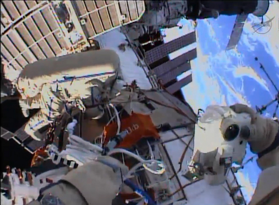 The beauty of Earth serves as the backdrop in this helmet camera view from a spacewalk by cosmonauts Alexander Misurkin and Fyodor Yurchikhin (who is visible in frame) as they worked outside the International Space Station on Aug. 22, 2013.