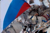 A cosmonaut holds a Russian flag during a spacewalk outside the International Space Station in honor of Russian Flag Day on Aug. 22, 2013.