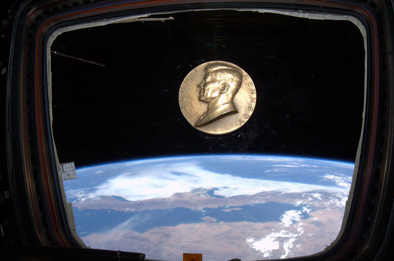 A bronze medallion emblazoned with the likeness of President John F. Kennedy floats on the International Space Station.