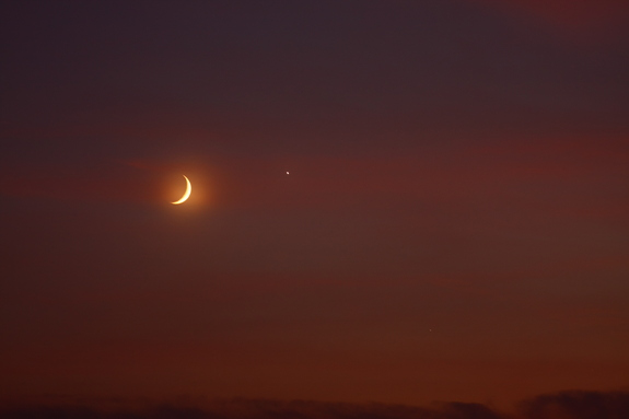 "Ben Nevills captured this photo of the moon and Venus over Worthington, Indiana. He took the image with a Canon 40D and Canon 100-400 mm lens on Sept. 8.  ""The weather was very humid and a slight layer of clouds didn't make for a very clear picture, but did add a little color,"" Nevills wrote SPACE.com in an email."