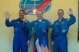 Expedition 37 NASA Flight Engineer Michael Hopkins, far left, Soyuz Commander Oleg Kotov and Russian Flight Engineer Sergey Ryazanskiy, far right, wave and give the thumbs up following a press conference held at the Cosmonaut Hotel, on Tuesday, Sept. 24, 2013, in Baikonur, Kazakhstan.