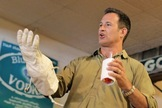 Dogfish Head founder Sam Calagione compares an ILC spacesuit glove to Celest-jewel-ale's spacesuit koozie.