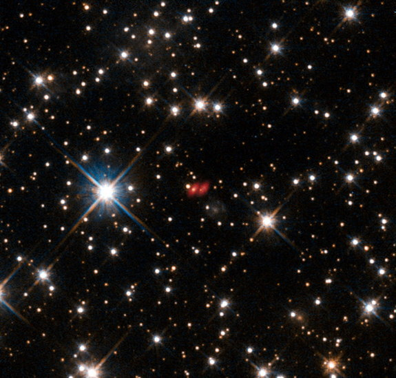 This image from the NASA/ESA Hubble Space Telescope shows the distant active galaxy PKG 1830-211. It shows up as an unremarkable looking star-like object, hard to spot among the many much closer real stars in this picture. Recent ALMA observations show both components of this distant gravitational lens and are marked in red on this composite picture. Image released Oct. 16, 2013.