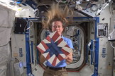 NASA astronaut Karen Nyberg displays the star-theme quilt block she created aboard the International Space Station.