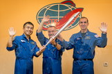Expedition 38 Flight Engineer Koichi Wakata of the Japan Aerospace Exploration Agency, left, Soyuz Commander Mikhail Tyurin of Roscosmos, and Flight Engineer Rick Mastracchio of NASA, right, smile and wave as they hold an Olympic torch that will be flown with them to the International Space Station, during a press conference held Wed., Nov. 6, at the Cosmonaut hotel in Baikonur, Kazakhstan.
