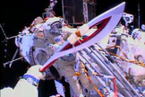 The Olympic torch is seen from the helmet camera of Russian cosmonaut Oleg Kotov in this view from a spacewalk on Nov. 9, 2013. Cosmonaut Sergey Ryazanskiy is seen awaiting the torch, which will be used in the 2014 Winter Games in Sochi, Russia.