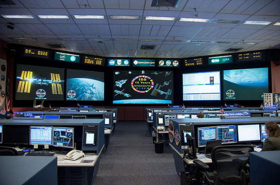 View inside the space station flight control room at NASA's Johnson Space Center in Houston. Displayed on the front screen, images celebrating the International Space Station's 15 years.
