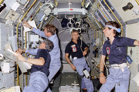 STS-9 crew members working on science experiments inside the European Spacelab 1 module, November 1983.