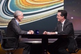 Voyager project Ed Stone speaks with host Stephen Colbert against a backdrop image of Saturn's rings on Dec. 3, 2013