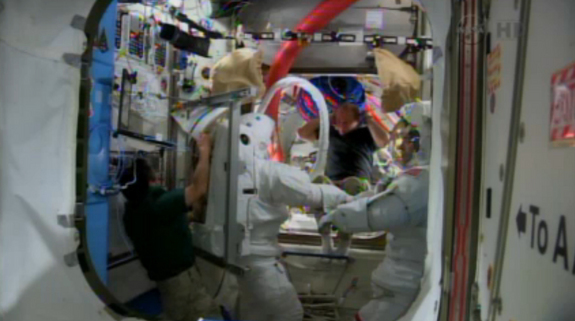 NASA astronauts Rick Mastracchio and Mike Hopkins (in suits) try on their spacesuits inside the International Space Station on Dec. 16, 2013 to prepare for a potential spacewalk repair of the outpost's cooling system.