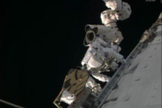 NASA astronaut Rick Mastracchio stands on the International Space Station's robotic arm during an urgent spacewalk to fix the station's vital cooling system.