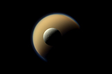 Saturn's largest and second largest moons, Titan and Rhea, appear to be stacked on top of each other in this true-color scene from NASA's Cassini spacecraft released on Dec. 23, 2013. The north polar hood can be seen on Titan appearing as a detached layer at the top of the moon on the top right. This view looks toward the Saturn-facing side of the smaller Rhea.