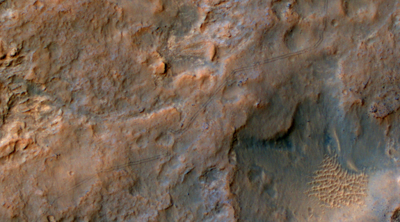 Two parallel tracks left by the- wheels of NASA's Curiosity Mars rover cross rugged ground in this portion of a Dec. 11, 2013, observation by the High Resolution Imaging Science Experiment (HiRISE) camera on NASA's Mars Reconnaissance Orbiter. The rover itself does not appear in this part of the HiRISE observation. Image released Jan. 9, 2014.