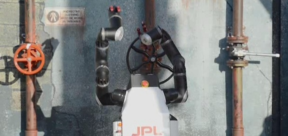 This image is a screengrab from a video showing Jet Propulsion Laboratory's RoboSimian turning a wheel at the DARPA Robotics Challenge in December 2013.