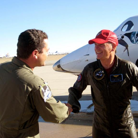 "Former NASA space shuttle commander Rick ""CJ"" Sturckow smiles and shakes hands after flying Virgin Galactic's SpaceShipTwo to a landing at California's Mojave Air and Space Port after a glide test flight on Jan. 17, 2014."