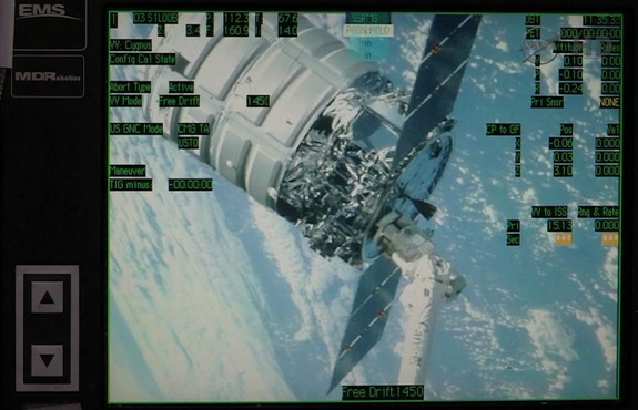 A monitor on the robotics workstation in the cupola provides the Expedition 38 crew with a view of Cygnus at the end of the International Space Station's robotic arm. Image released Feb. 18, 2014.