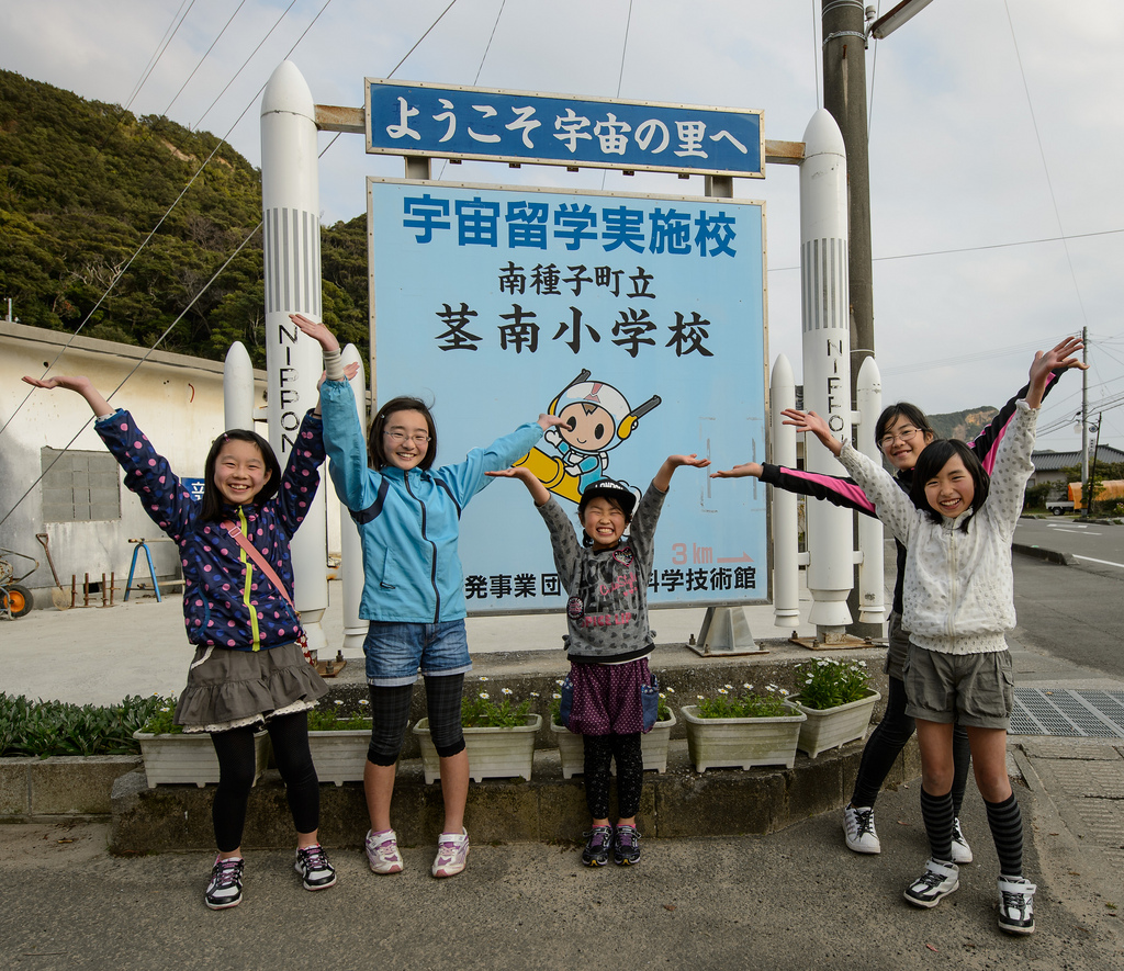 School Girls Pose in Front of Sign Featuring Mascot 'Chuta-Kun'