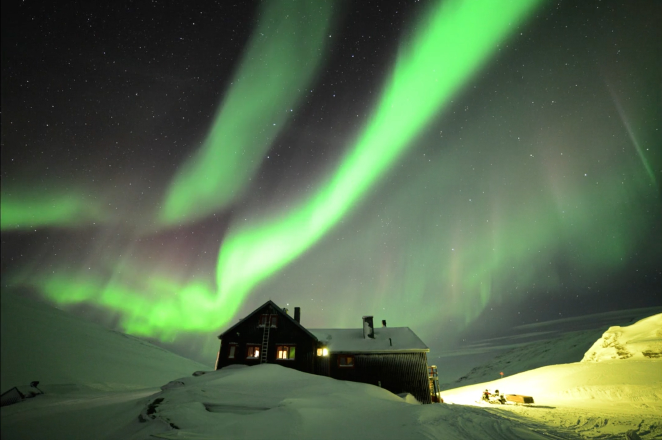 Auroras Glow Over Hotel in Swedish Lapland by Chad Blakley