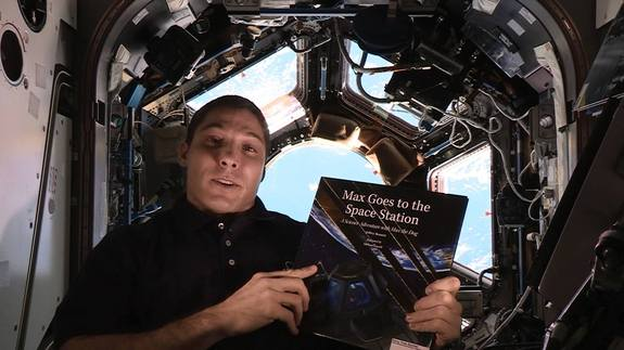 "NASA astronaut Mike Hopkins holds the book ""Max Goes to the Space Station"" inside the real-life space station's Cupola observation deck. The book, written by author Jeffrey Bennett, is part of Story Time From Space."